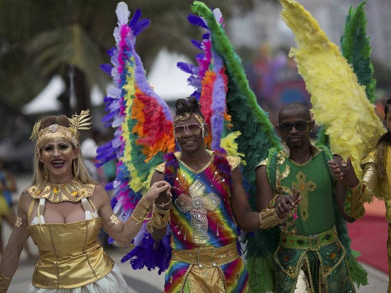The Copacabana beach in Rio de Janeiro was packed to capacity on November 15 for the city's 20th Gay Pride Parade. People pose for pictures as they wear feathered angel wings during the parade. (AP)