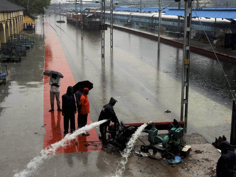 Railway workers pumping out the rainwater from tracks at inundated Vyasarpadi railway station after heavy rains in Chennai on Friday. (PTI)