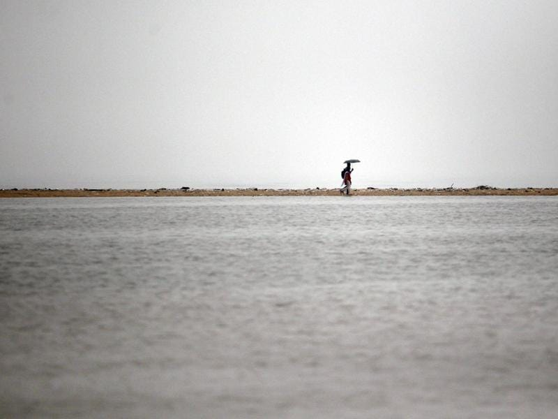 Indian couple walks on a dry stretch of land on the waterlogged Marina Beach after heavy rainfall in Chennai. (AP)