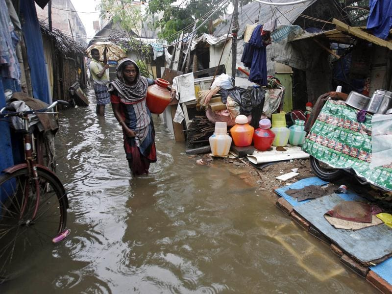 Woman carries a vessel of water at a slum dwelling as it rains in Chennai. (AP)