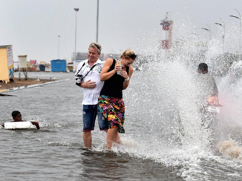 Foreigners trying to move away as a motorcycle splashes water at Marina Beach in Chennai on Saturday. (PTI)