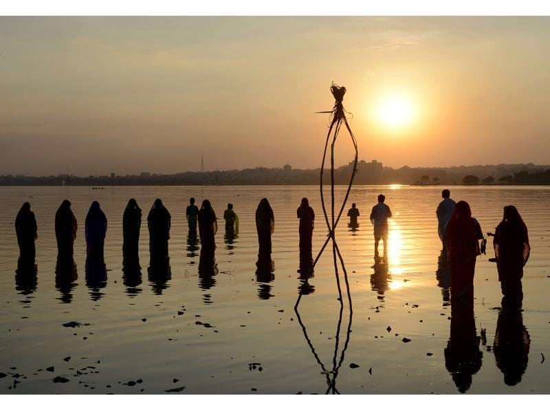 Indian Hindu devotees offer prayers to the sun during the Chhath festival on the banks of the Hussain Sagar Lake in Hyderabad. (Noah Seelam/AFP Photo )