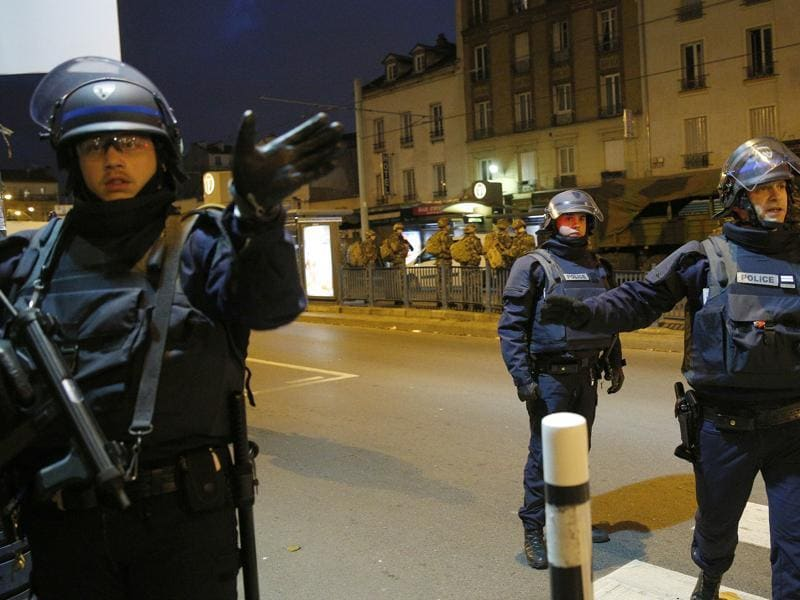 Police forces prepare in St. Denis, a northern suburb of Paris. Authorities in the Paris suburb of St. Denis were telling residents to stay inside during a large police operation near France's national stadium that two officials said was linked to last week's deadly attacks.  (AP Photo)