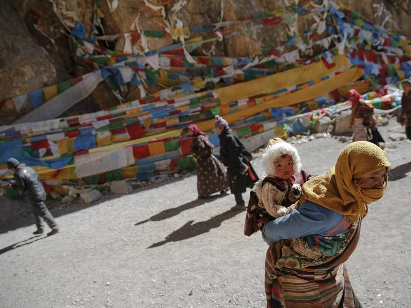 A Tibetan woman carries a child as they visit Namtso lake. Itis not only the highest saltwater lake in the world but also considered sacred, attracting throngs of devotees and pilgrims.  (REUTERS)