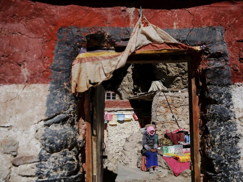 A Tibetan woman sits in front of a house built in a rock at the shores of Namtso lake.  (REUTERS)