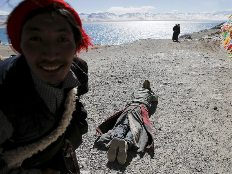 A Tibetan looks at the camera as other one prostrates himself at the lake.  (REUTERS)