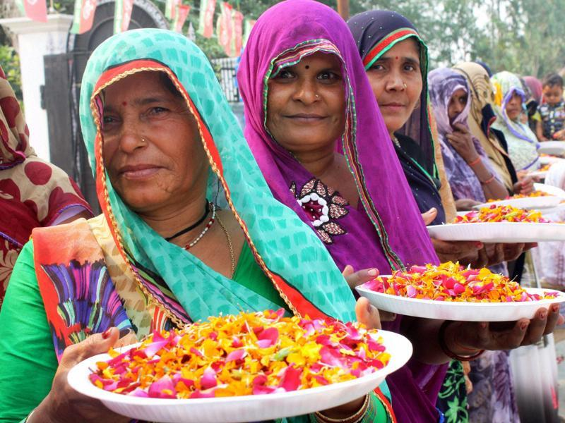 Village women wait to welcome SP chief Mulayam Singh Yadav on his 77th birthday in Saifai on Saturday.  (PTI Photo)
