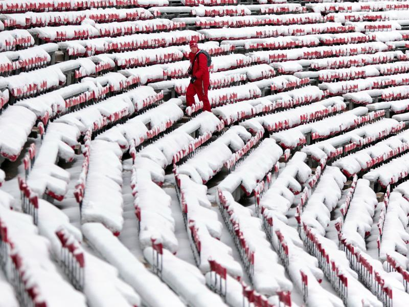 A man in Wisconsin, USA trudges through the snow-covered west stands before a football game, Saturday, November 21, 2015.  (AP)