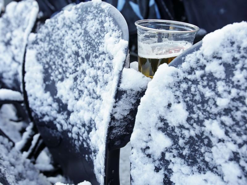 A glass of beer sits between snow-covered seats prior to football game between teams from Chicago and Denver in Chicago, USA on November 22, 2015. (AFP)