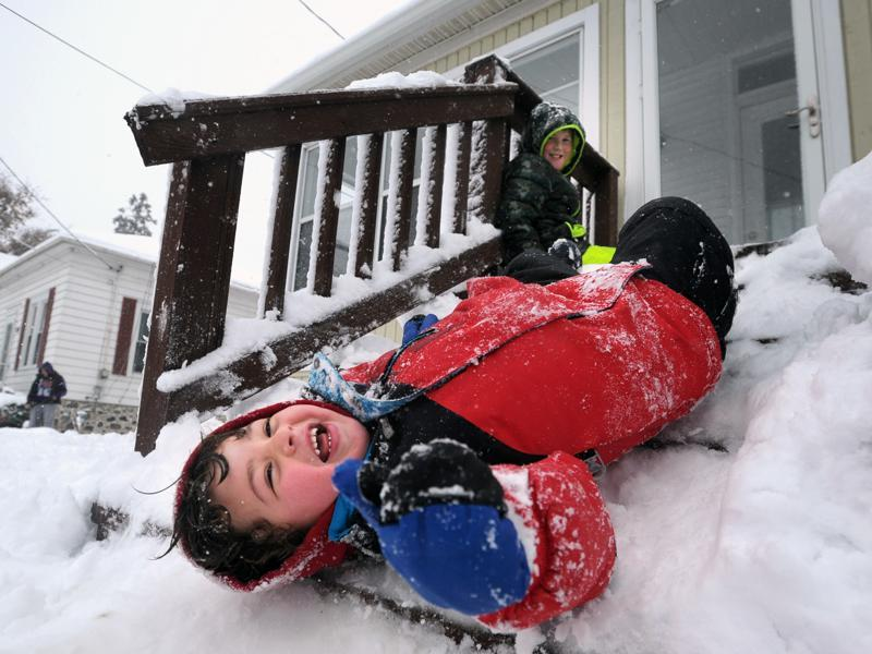 Luca Damato of Wisconsin slides down packed snow on his stairs as another child looks on while they play outside their home, Nov. 21, 2015. The first significant snowstorm of the season blanketed some parts of the Midwest in the US with more than a foot of snow causing hazardous travel conditions and flight delays. (Sean Krajacic/The Kenosha News)  (AP)