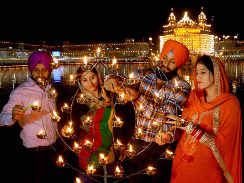 Devotees illuminate candles at the Golden Temple on the occasion of the 547th birth anniversary of Guru Nanak Dev, in Amritsar. (PTI Photo)
