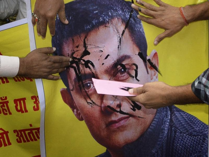 BJP activists paint a poster of Bollywood actor Aamir Khan with black color as they protest over actor's intolerance remark, in Patna, Bihar on Tuesday, November 24, 2015.  (Photo by Santosh Kumar/ Hindustan Times)