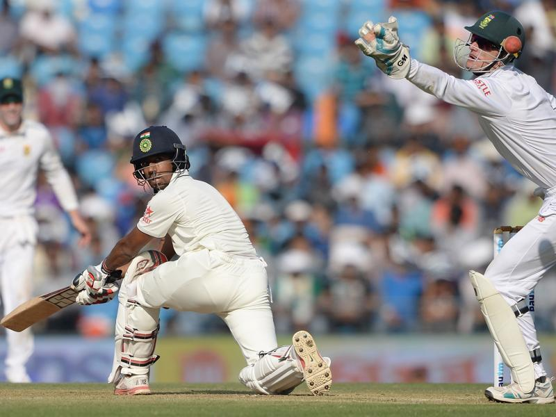 India's Wriddhiman Saha looks back after playing a shot as Dane Vilas attempts to catch the ball.  (AFP Photo)
