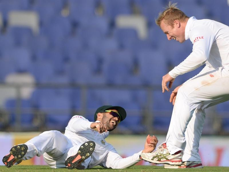 South Africa's Simon Harmer (R) runs towards teammate JP Duminy (L) after he took a catch to dismiss India's Wriddhiman Saha on the first day of the third Test match at The Vidarbha Cricket Association Stadium in Nagpur on November 25, 2015.  (AFP Photo)