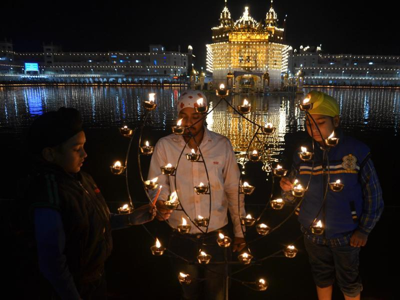 Children lighting candles at a lit-up Golden Temple in Amritsar on Wednesday.  (Sameer Sehgal/HT Photo)
