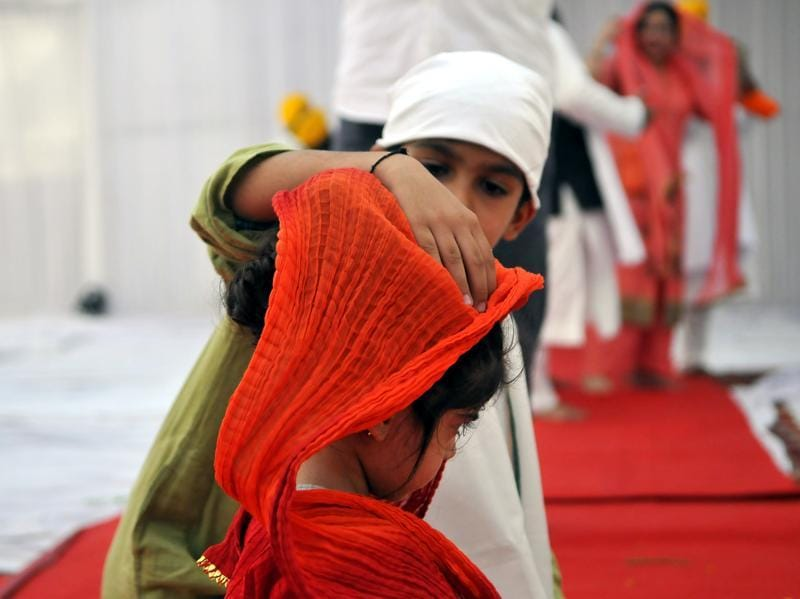 A small kid Saveer, 8, helps his sister Amora (3) manage the 'dupatta', which is believed to be mandatory while praying in a Sikh holy temple.  (Abhinav Saha/HT Photo)