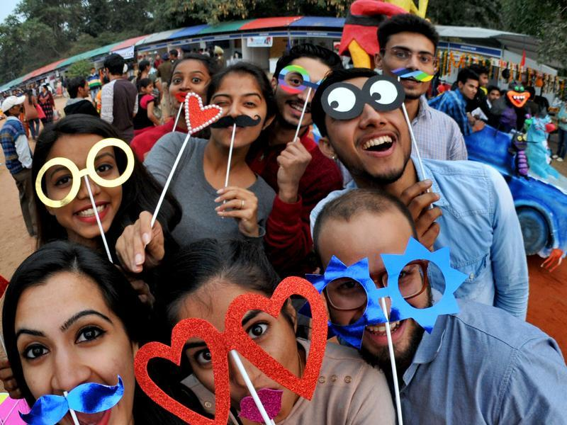 Youngsters having a little fun with  colourful photo props during at the Chandigarh Carnival. (Ravi  Kumar/HT )