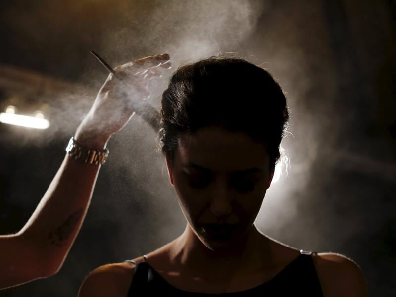 A hairdresser sprays hair spray on a model backstage, creating a stunning effect for the photographer to use. (REUTERS)