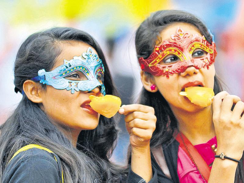 Girls enjoy some ice-cream during the Chandigarh Carnival being held at the Leisure Valley. (Keshav singh/HT Photo)