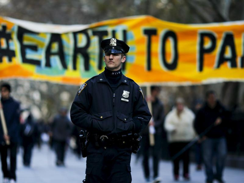 A New York Police officer keeps an eye on protesters while they take part in a protest about climate change around New York City Hall at lower Manhattan, New York. (Reuters Photo)