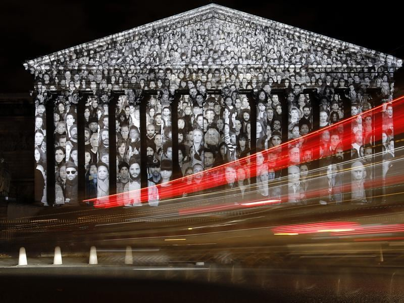 Cars pass by the National Assembly in Paris, where a projection of French artist JR is displayed as part of the 2015 Paris Climate Conference. (AP Photo)