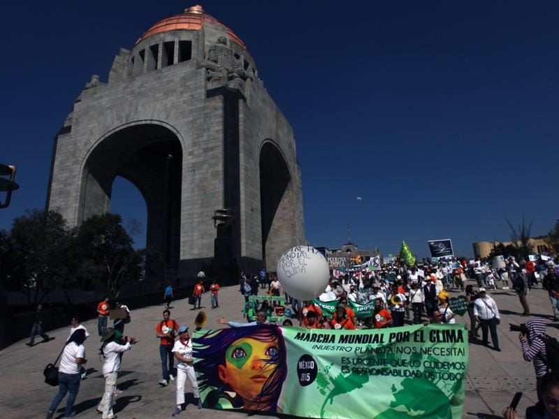 People march during a protest for Global Climate next to a monument to the Revolution, in Mexico City.  (AP Photo)