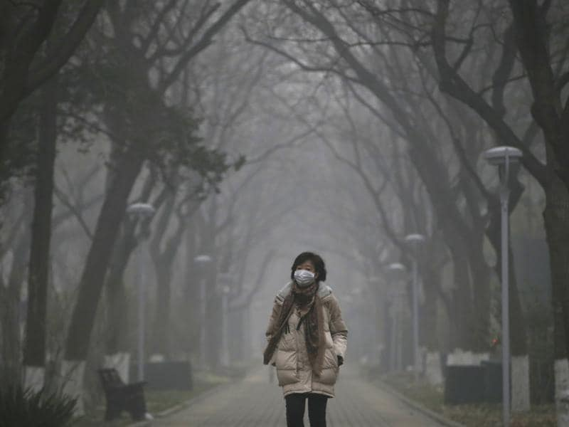 A woman wearing a mask walks as smog covers China's capital Beijing. (REUTERS Photo)