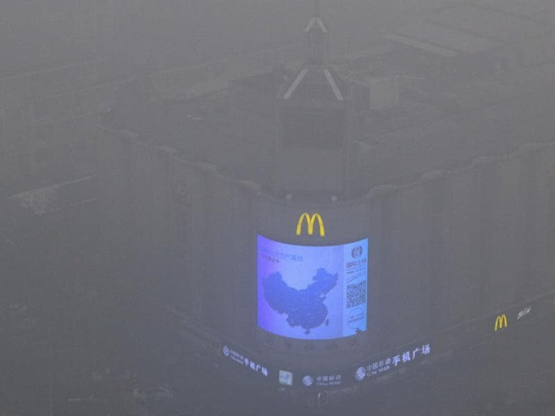 A video display on the side of a building shows a map of China amid heavy pollution and fog in Beijing. (AP Photo)