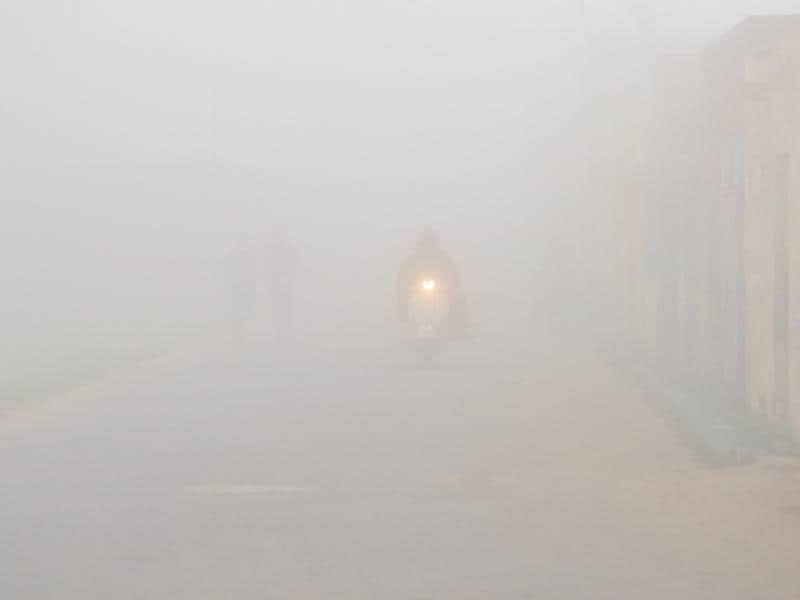 A man on his two-wheeler on a foggy morning in Dhanowali village on the outskirts of Jalandhar on Tuesday. (Pardeep Pandit/HT Photo)