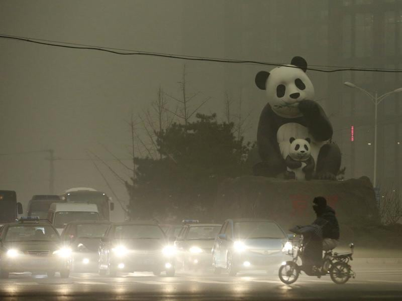 A resident rides an electric bicycle across a street amid heavy smog as vehicles wait for a traffic light next to a statue of pandas, a landmark of the Wangjing area in Beijing. (REUTERS  Photo)