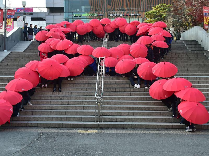 South Korean middle school students hold umbrellas as they form a giant red ribbon during a ceremony to mark World AIDS Day in Seoul. (AFP)