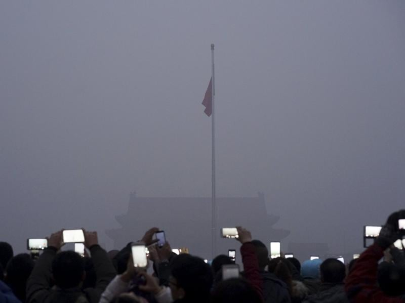Visitors use mobile phones to take pictures and videos as they watch a flag raising ceremony at the Tiananmen Square amid heavy smog in Beijing. (REUTERS Photo)