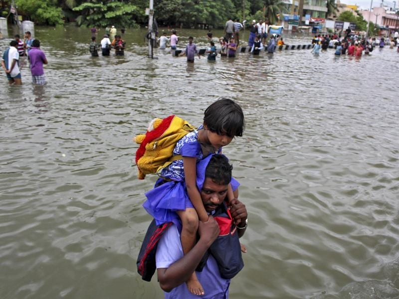 A man carries a girl through a flooded road in Chennai. The heaviest rainfall in over a century caused massive flooding across Tamil Nadu. (REUTERS)