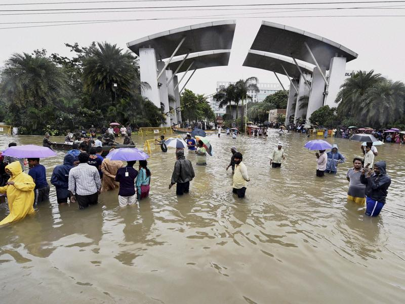 People wade through waterlogged roads after heavy rains inundated several areas, at Porur in Chennai. (PTI Photo)