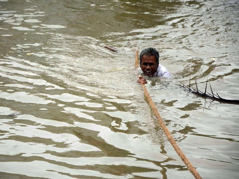 A man clings to a rope as he makes his way through floodwaters in Chennai. (AFP)