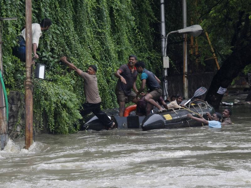 Rescuers try to evacuate a man stranded in the floods by an over-flowing Adyar River in Chennai. (AP)