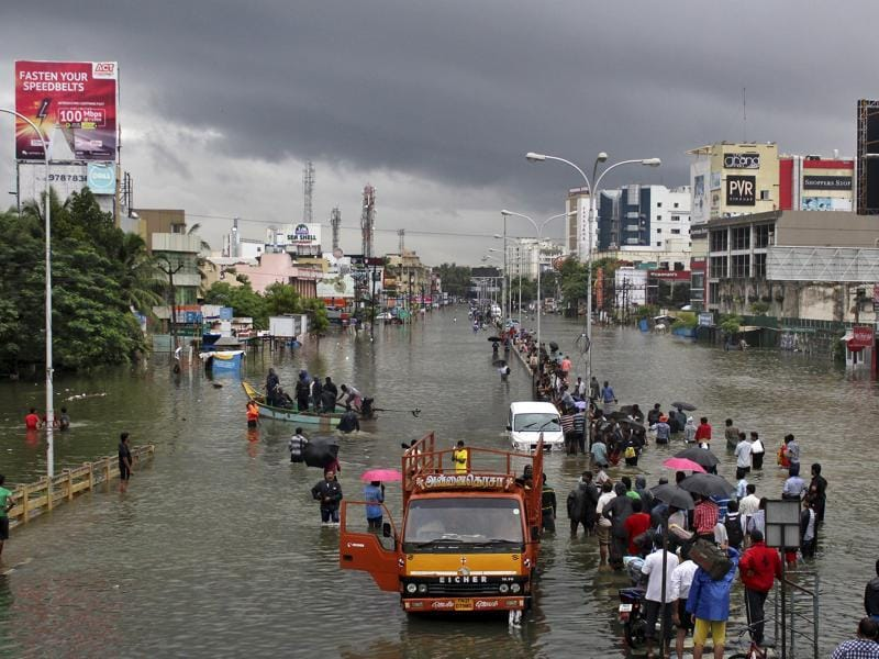 People stand on a flooded road in Chennai. The heaviest rainfall in over a century caused massive flooding across Tamil Nadu, driving thousands from their homes, shutting auto factories and paralysing the airport in the state capital Chennai.   (Reuters Photo)
