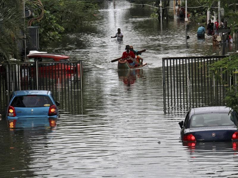 People travel on a boat as they move to safer places through a flooded road in Chennai. The heavy rains drove thousands from their homes, shutting auto factories and paralysing the airport. (REUTERS)