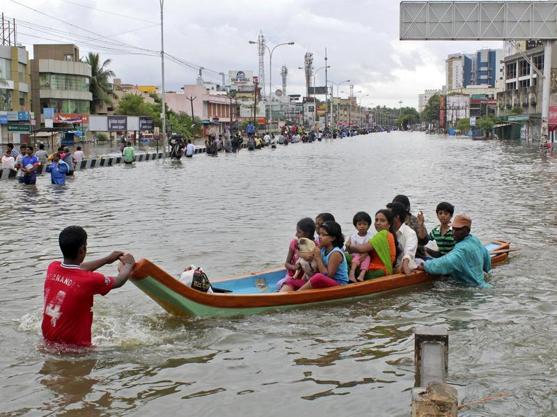 People travel on a boat as they move to safer places through a flooded road in Chennai. (REUTERS)