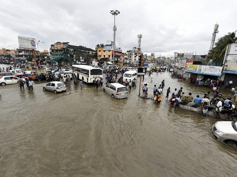 Vehicles move on the waterlogged road during heavy rains in Chennai on Wednesday.  (PTI )