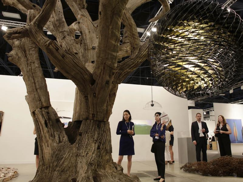 A tree sculpture by artist Ai Weiwei and a globe sculpture by artist Olafur Eliasson are displayed at Galerie neugerriemschneider, Wednesday, December 2, 2015, at Art Basel Miami Beach, in Miami Beach, Florida. (AP)