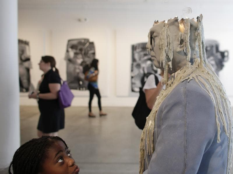 A girl looks up at a sculpture by artist Urs Fischer titled Zhou Yinghua, at an exhibit called Unrealism, during Miami Art Week, Thursday, December 3, 2015, in the Design District neighbourhood of Miami. (AP)