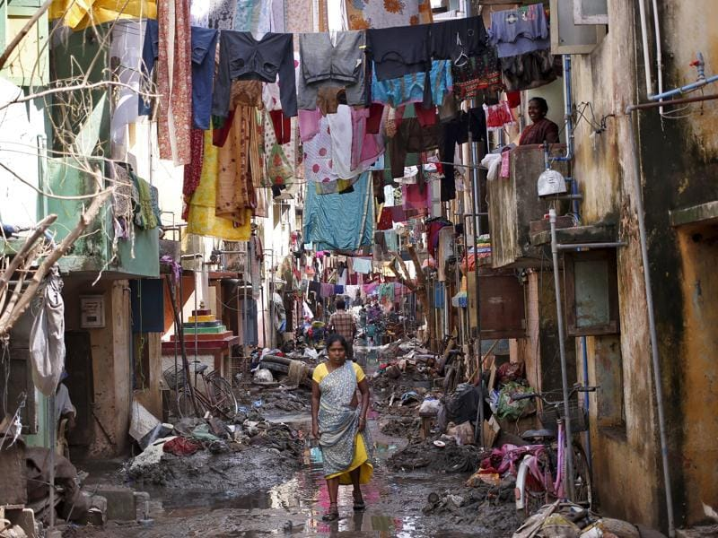 A woman walks in an alley filled with mud and debris to collect relief goods as clothes are hung out to dry after flood waters receded in Chennai. (REUTERS Photo)