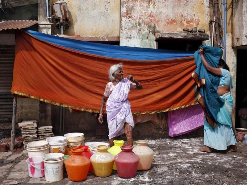 A woman waits outside her house for a water tanker to fill her containers with drinking water in Chennai. (REUTERS Photo)