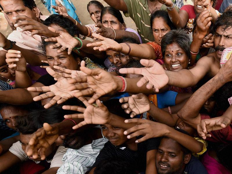 Resident of the low-income Kotturpuram area wait in line for relief materials. (PTI Photo)