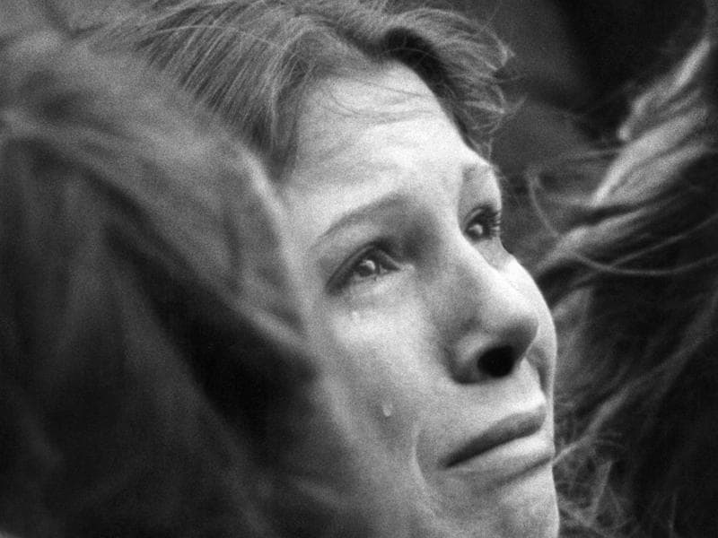 A woman weeps during a ten minute silent vigil for John Lennon held in front of Trinity Church in Boston on December 14, 1980. An estimated crowd of 2,000 people came to honour the former Beatle. (AP)