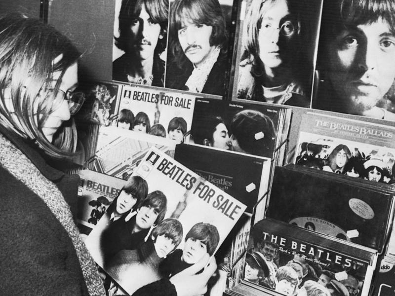 In this December 10, 1980 photo, a Beatles fan holds a vintage record album Beatles for Sale in a re cord shop in Stuttgart, Germany. (AP)