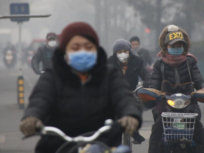 People wearing protective masks ride bicycles in the morning on an extremely polluted day in Beijing. (REUTERS)