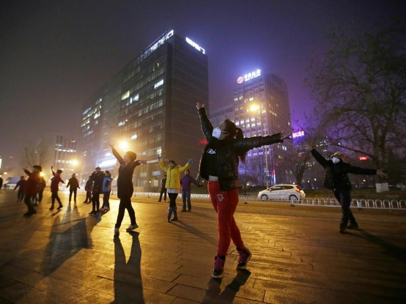 Women wearing masks and other residents dance during their daily exercise amid the heavy smog in Beijing. (REUTERS)