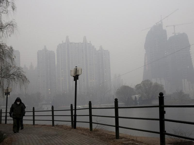 A man wearing a protective mask takes a walk at a park in the morning on an extremely polluted day in Beijing. (REUTERS)